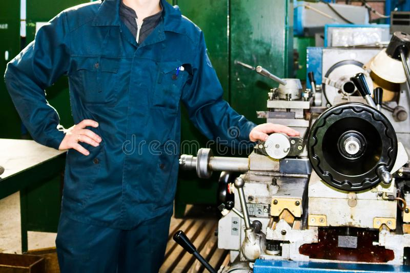 A man working in a robe, overalls stands next to an industrial lathe for cutting, turning knives from metals, wood other materials royalty free stock photos
