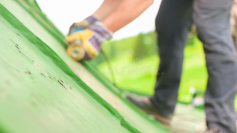 Man Working on the Roof, Sandering Paint stock images