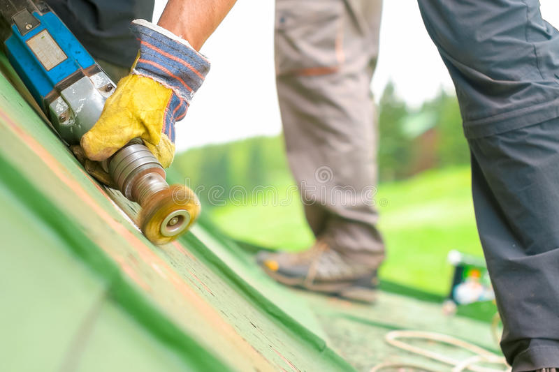 Man Working on the Roof, Sandering Paint stock photography