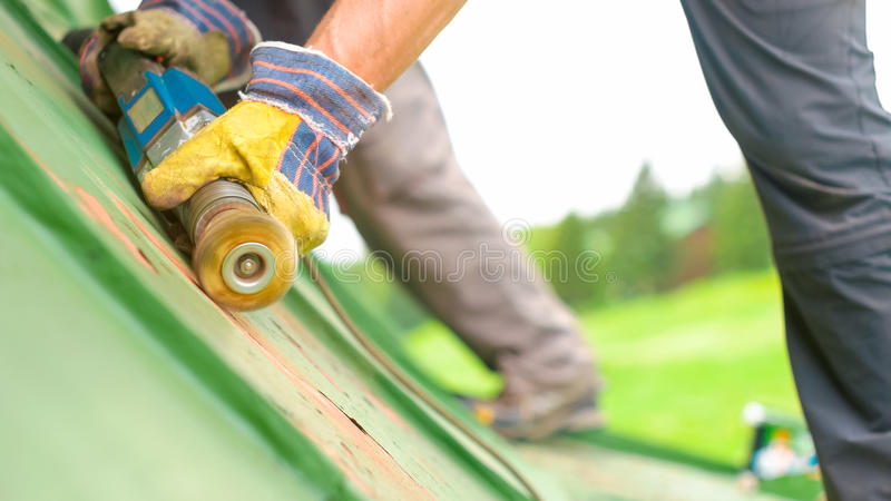 Man Working on the Roof, Sandering Paint royalty free stock photos
