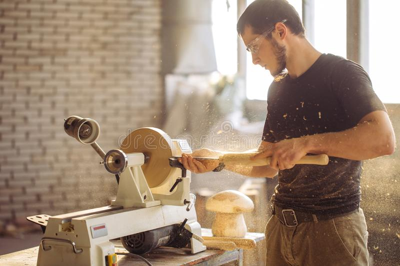 Man working at small wood lathe, an artisan carves piece of wood royalty free stock photo