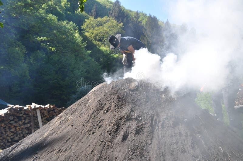 Man working on smoking charcoal-kiln stock photo