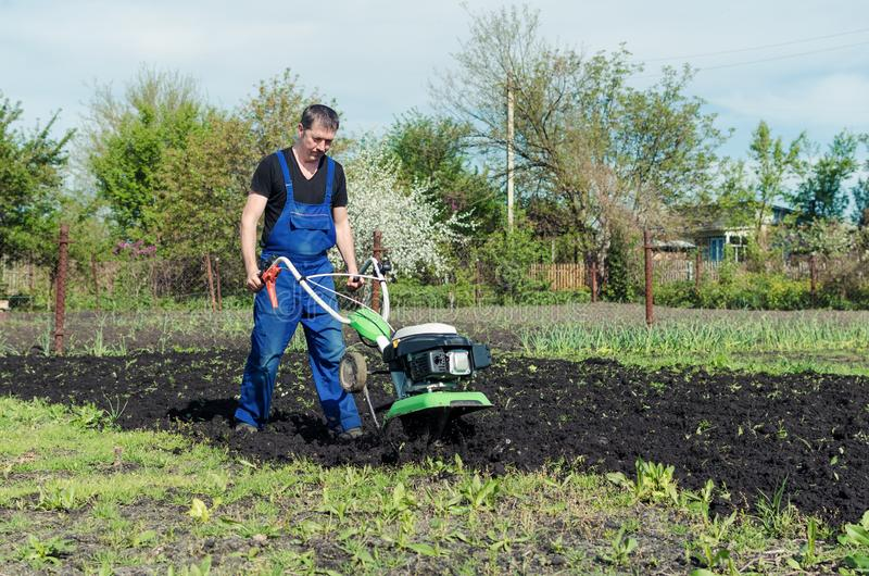 Man working in the spring garden with tiller machine stock image
