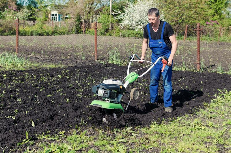 Man working in the spring garden with tiller machine stock photo