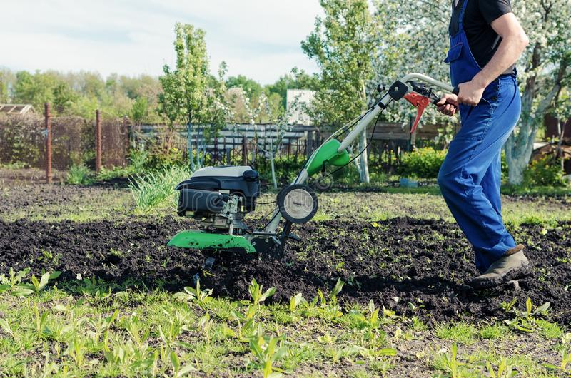 Man working in the spring garden with tiller machine stock photography