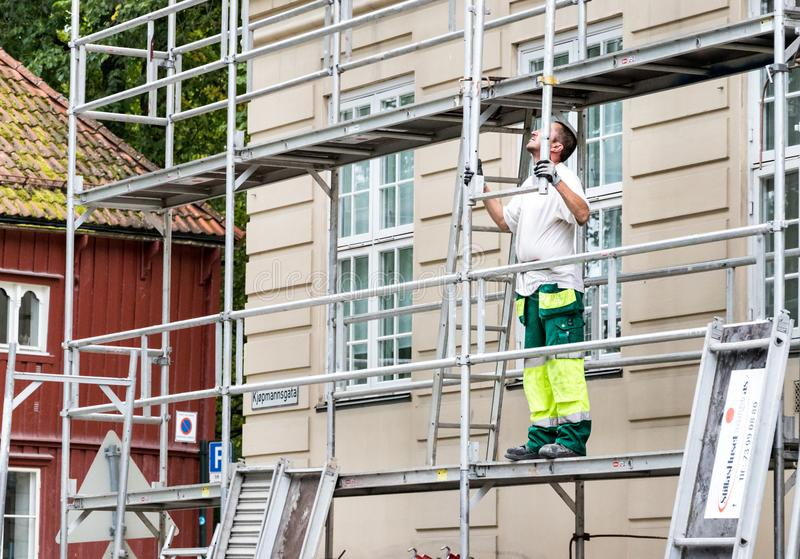 A man working standing on a scaffolding in the city center of Trondheim stock photos