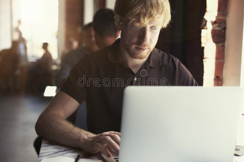 Man working at sunny office on laptop while sitting in cafe having coffee. Concept of young business people working in public spac. E or co-working stock photo