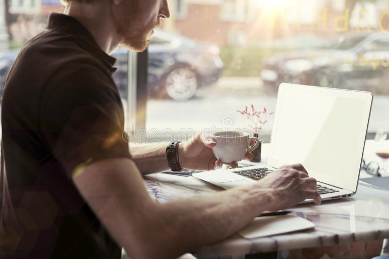 Man working at sunny office on laptop while sitting in cafe having coffee. Concept of young business people working in public stock photography