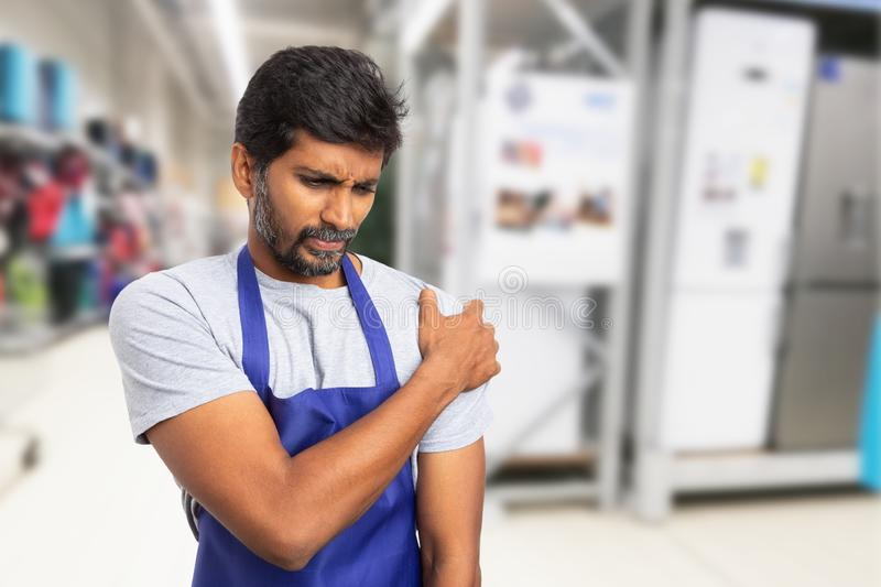 Man working at supermarket holding painful shoulder stock photo