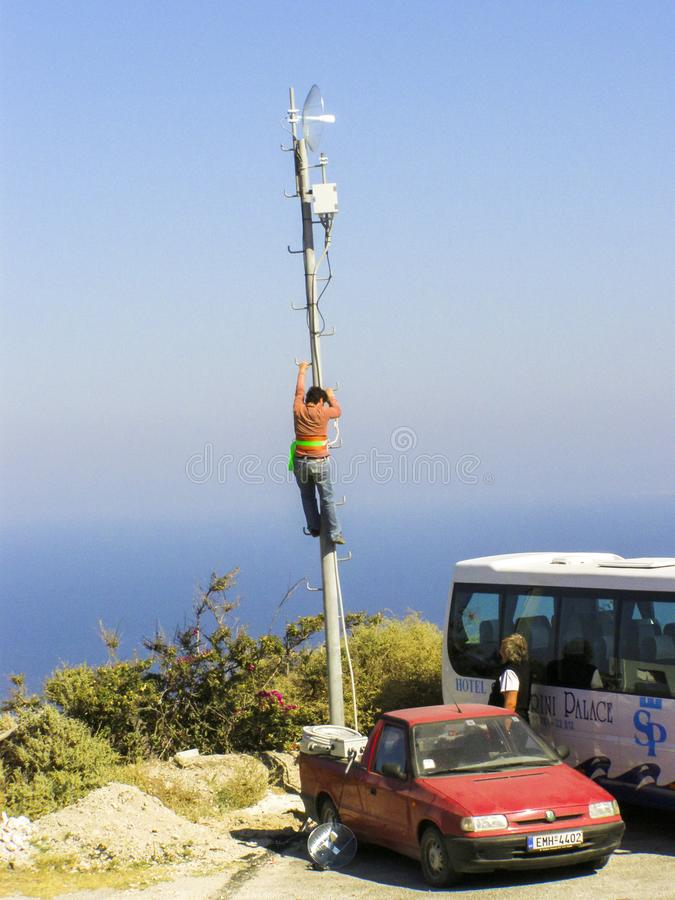 Man working on a telecommunication pole in Crete, Greece. A working is performing a maintenance work in dangerous conditions on a communications pole in Crete stock photography