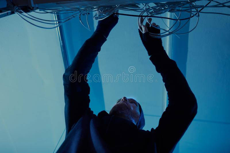 Man working with wires. Low angle view of young man in dark clothing putting the wires in order in dark room royalty free stock photos