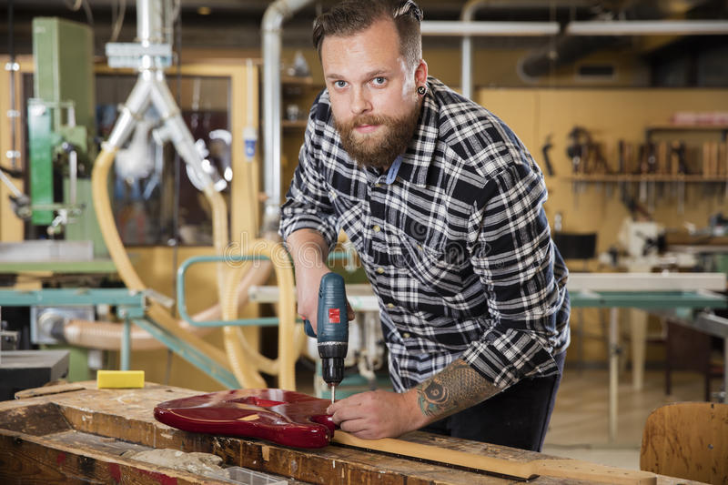Man working at workshop with guitar stock photos