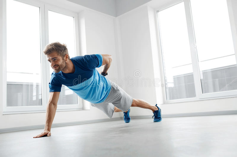Man Workout Exercises. Fitness Male Model Doing Push Ups Indoors. Man Workout Exercises. Handsome Fitness Male Model With Athletic Muscular Body In Fashion stock photography