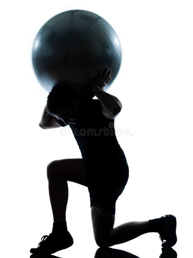 Man workout holding fitness ball. One n man workout holding fitness ball exercising workout aerobic fitness posture full length silouhette on studio isolated on stock photo