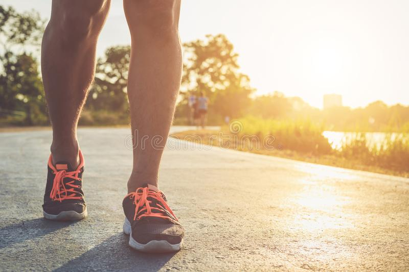 Man workout wellness concept : Runner feet with sneaker shoe run. Man workout wellness concept : Close up runner feet with sneaker shoe running on road in the stock images