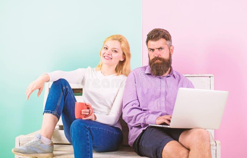 Man works as internet technologies expert on freelance. Freelance benefits. Girl enjoy drink while husband freelancer stock photo
