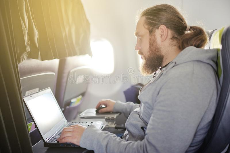 The man works behind the laptop in salon the plane. royalty free stock images