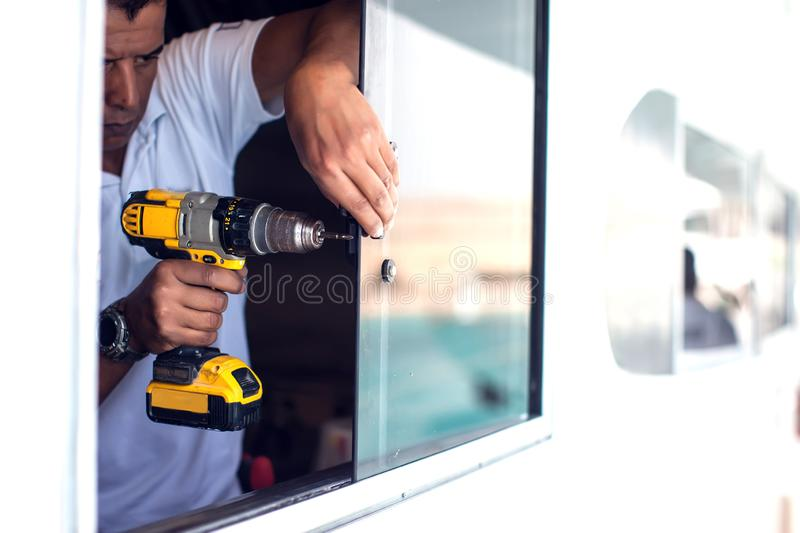 A man works with an electric screwdriver stock images