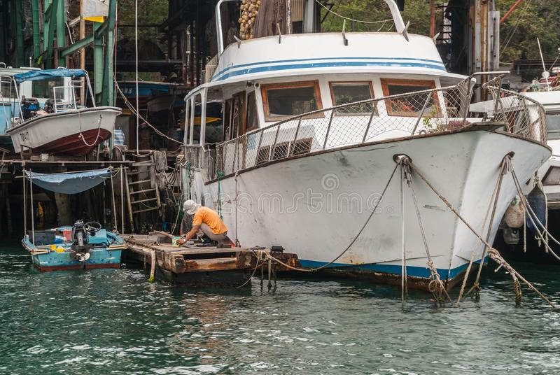 Man works on a houseboat in the harbor, Hong Kong, China. Hong Kong, China - May 12, 2010: Man works to restore a white yacht and houseboat docked along the stock photography