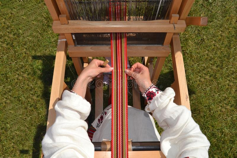 Man works on a knitting machine. stock photos