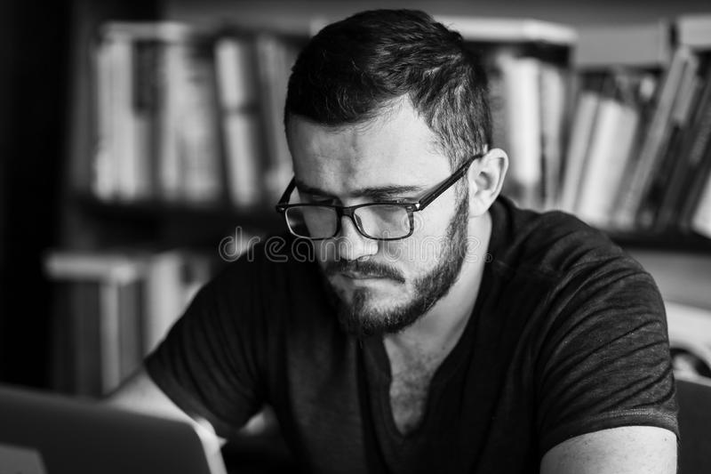 Man worn glasses. Software Engineer is sitting and working. He is looking into his laptop stock photo