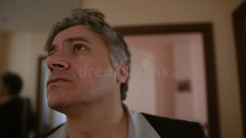 Man worried by strange noise apprehensively listening, hotel inspector, closeup stock image