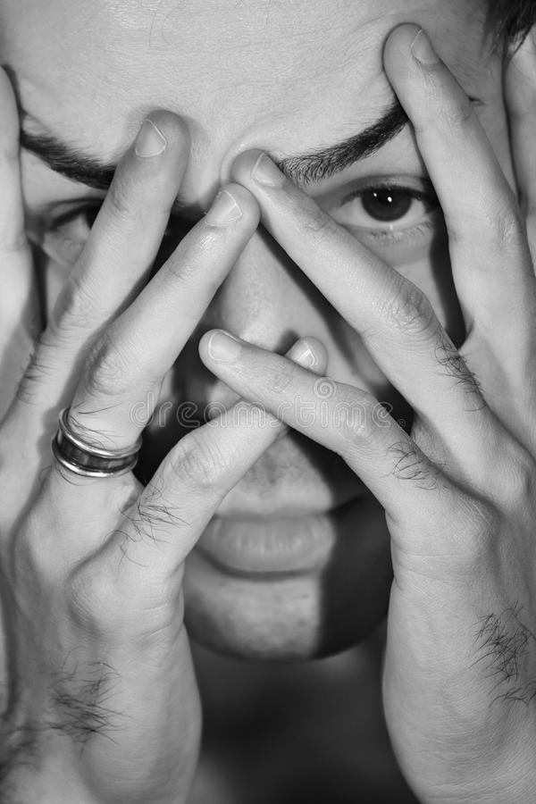 Man worried, stressed hides face. Shame and fear c stock photography
