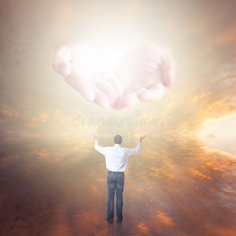 Man worshiping God. Hands with light coming from the sky stock photo