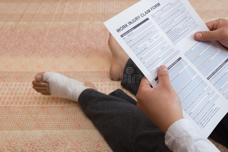 Man with a wrapped foot sitting on bed reading a work injury claim form. Man with a wrapped foot sitting on bed reading the work injury claim form stock photos