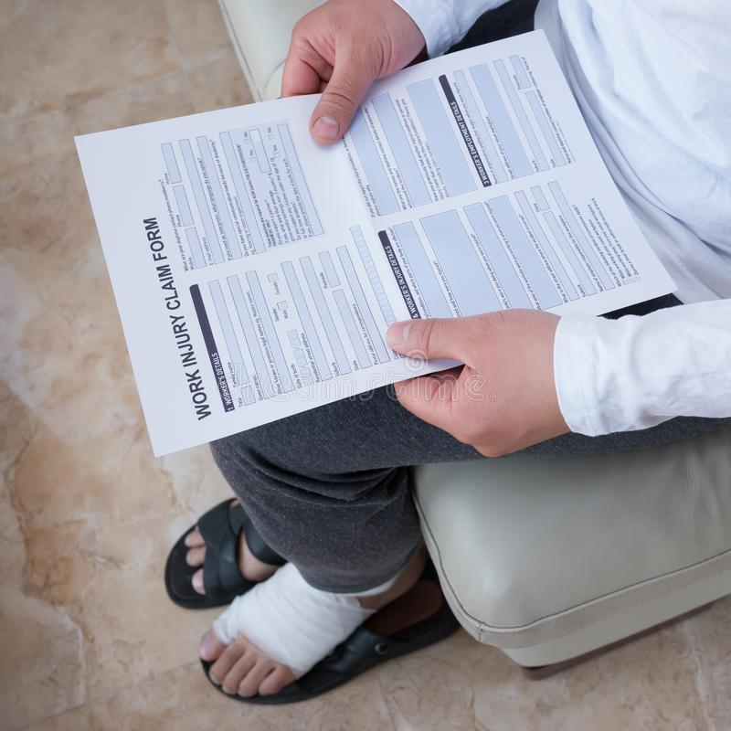 Man with a wrapped foot sitting on sofa reading work injury claim form. Man with a wrapped foot sitting on sofa reading the work injury claim form stock photos