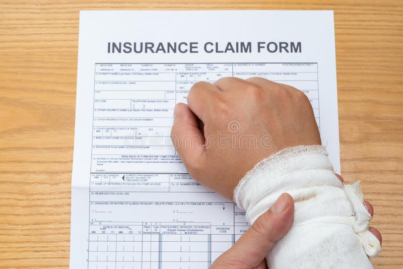 Man with wrapped hand reading a work injury claim form royalty free stock photos