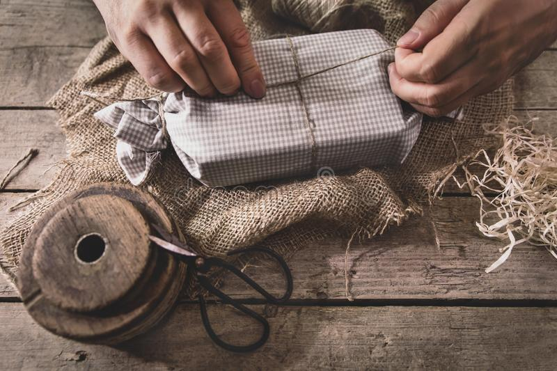 Man is wrapping a gift with natural materials and organic cotton, ecological and biodegradable stock image