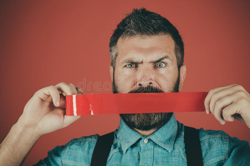 Man wrapping mouth by adhesive tape. censorship. Brutal bearded male. Mind control and propaganda. International Human. Right day. Concept freedom of speech and stock images