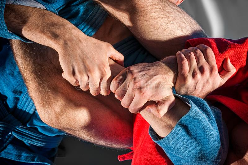 Man wrestler makes submission wrestling. Close-up two wrestlers of sambo and jiu jitsu in a blue and red kimono doing . Man wrestler makes submission wrestling stock photo