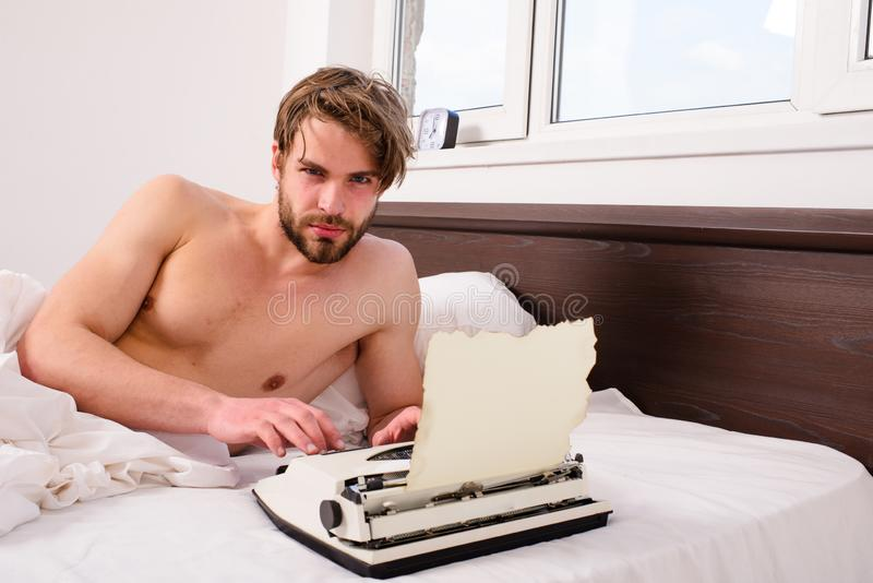 Man writer lay on bed white bedclothes working on new book. Writer author used to old fashioned machine instead of. Digital gadget. Morning inspiration concept stock photo
