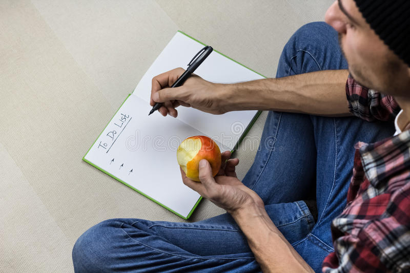 Man writes to do list in notebook stock photography