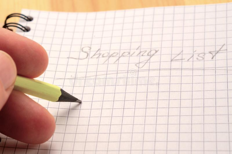 A man writes in yellow pencil in a notebook. Sign Shopping List. Top view stock photos