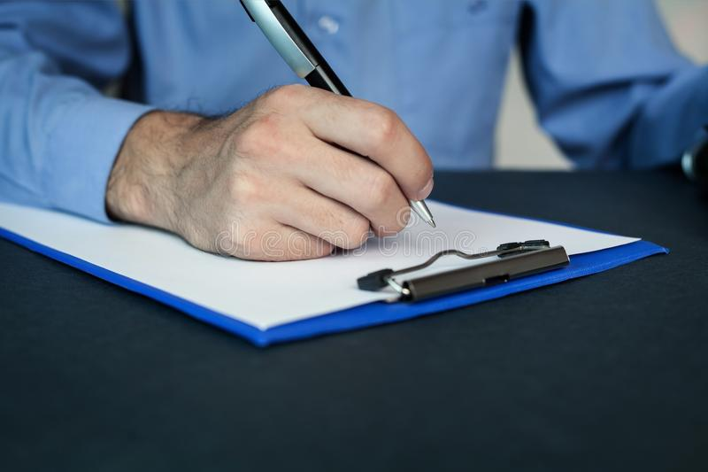 Man writing on a blank paper. stock photography