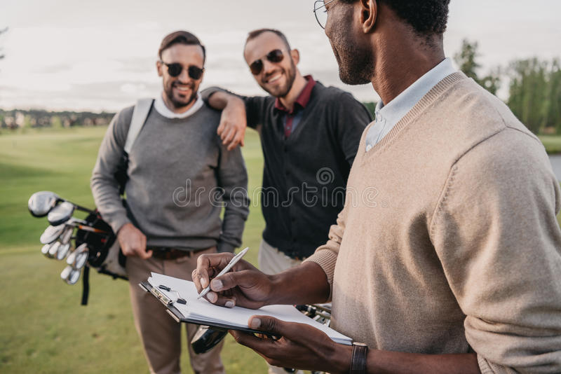 Man writing in clipboard while looking on two golf players stock images