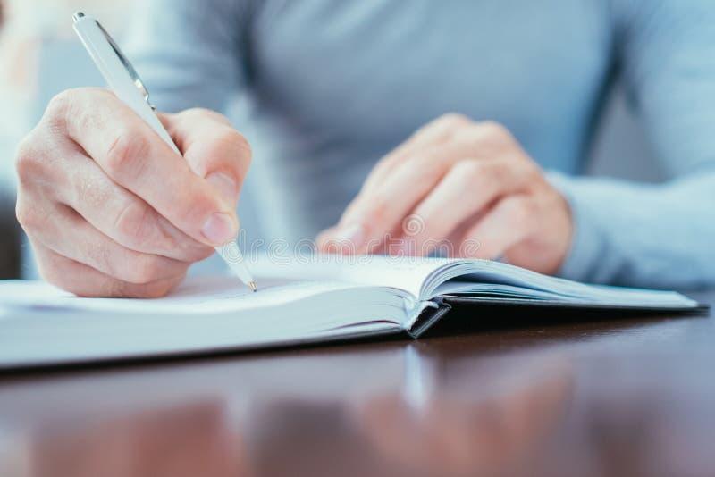 Man writing day planner work schedule organizer stock photo
