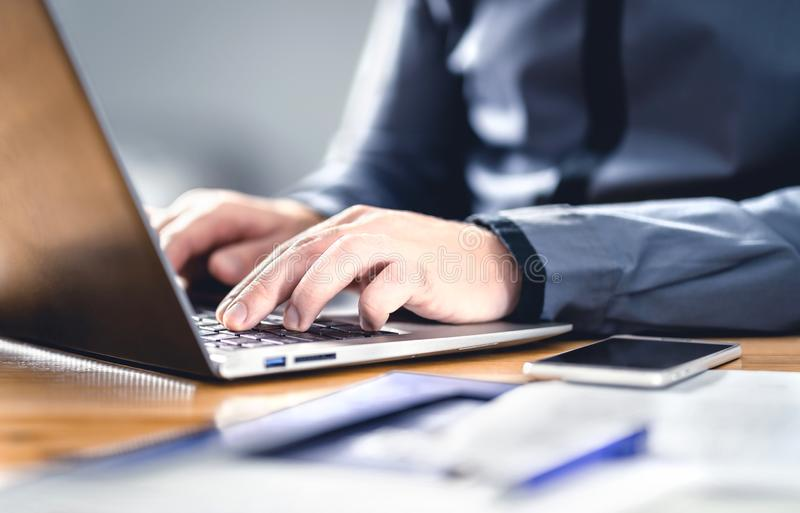 Man writing with laptop. Smart hipster guy with finance, market and business expertise. Freelance work with digital device. Phone on table and office desk stock images