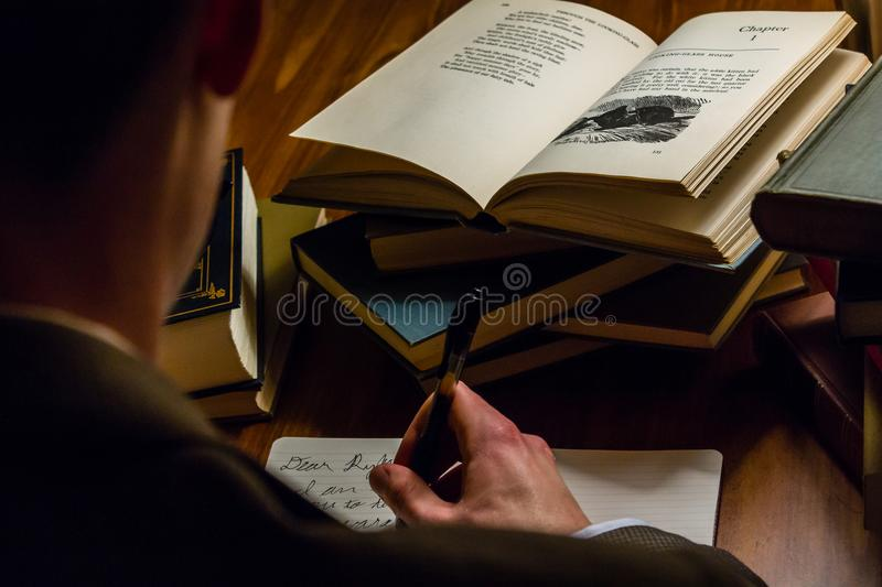 Looking over the shoulder of a man writing a letter while reading literary works stock photography
