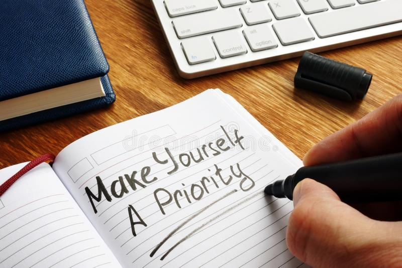 Man is writing Make yourself a priority stock photo
