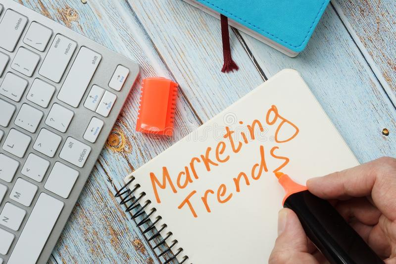 Man is writing marketing trends. In the book royalty free stock photography