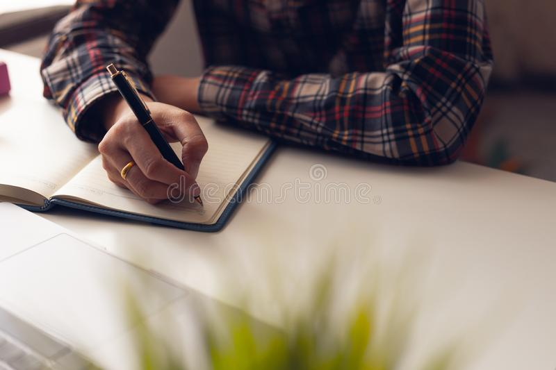The man is writing a message in the book on table. He is now sitting business plan. That has new idea in the morning. Concept idea planing and analyzes stock image
