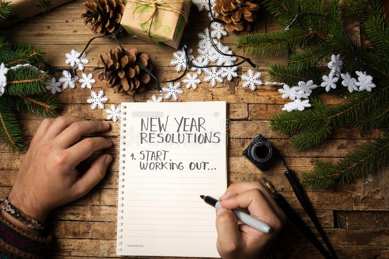 Man writing new year resolution on paper. Man writing start working out new year resolution stock image