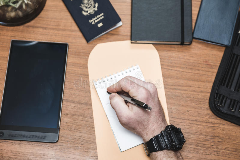 Man Writing Note on Desk. Man writing on a note pad with envelope, passport, tablet, check book, and other related accessories nearby stock photo