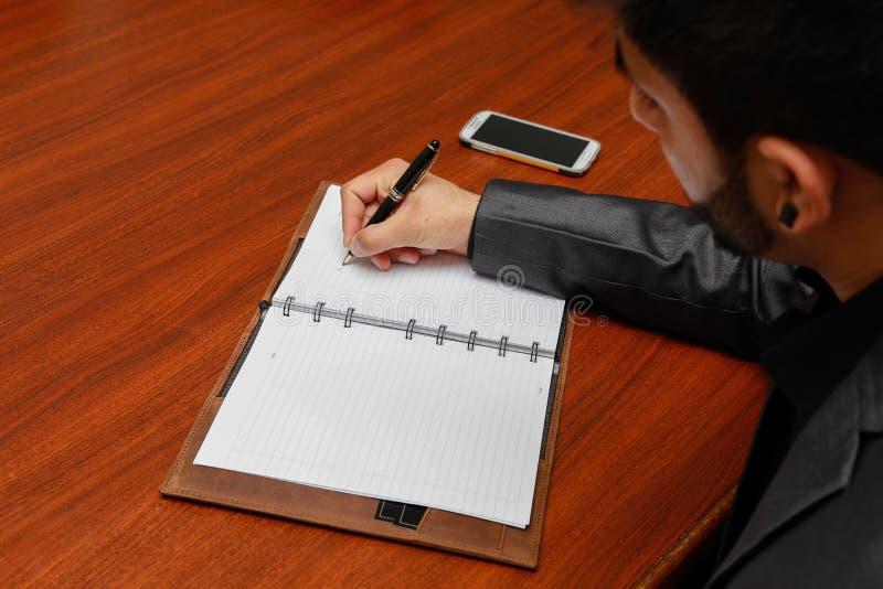 Man writing on notebook royalty free stock photos