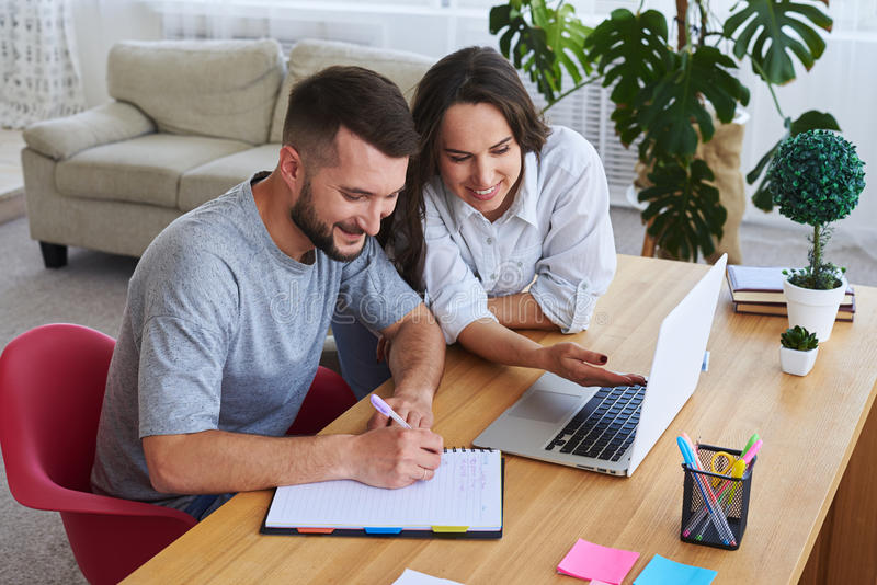Man writing in notebook while woman showing something to him in. High angle of men writing in notebook while women showing something to him in laptop royalty free stock photos