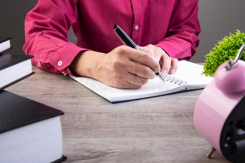 Man writing on notebook stock images